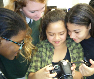3 Girls and an instructor viewing digital camera